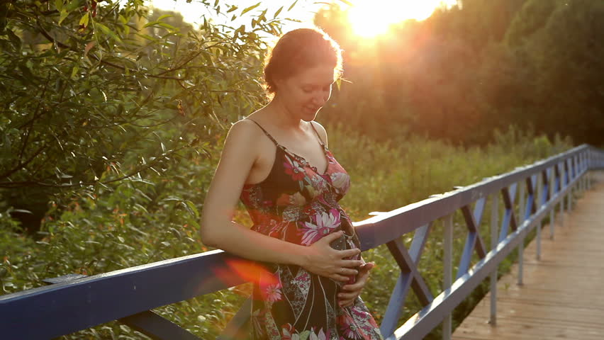 Happy pregnant woman caressing belly