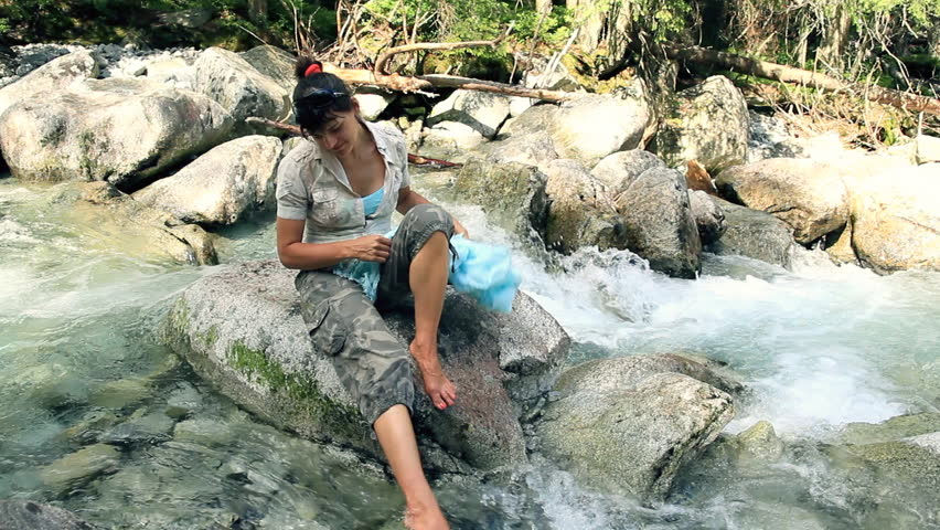 Woman relaxing on the rocks in the forest stream   - HD stock video clip