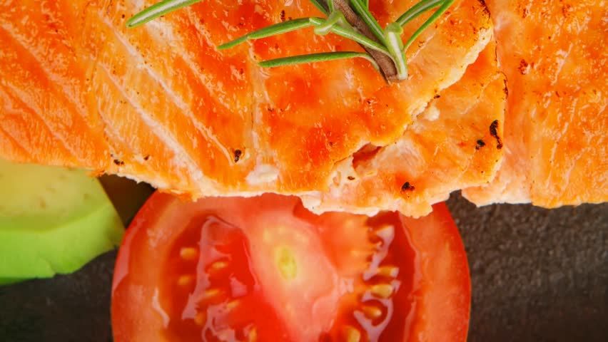 healthy sea food: grilled salmon on iron pan over wooden plate with lemon avocado and tomatoes 1920x1080 intro motion slow hidef hd