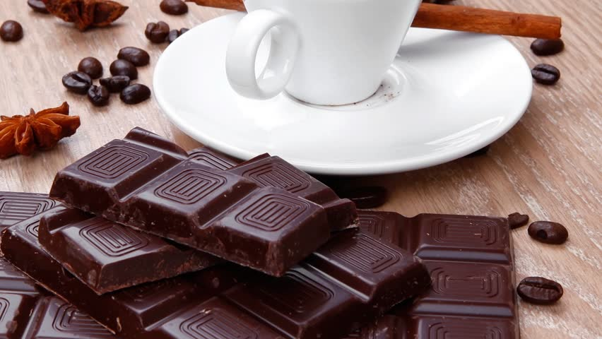 sweet hot drink : black coffee in small white cup with beans on a wooden table with stripes of dark chocolate and cinnamon sticks 1920x1080 intro motion slow hidef hd