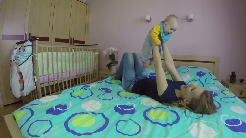adorable baby boy playing in bedroom and hugging his mom