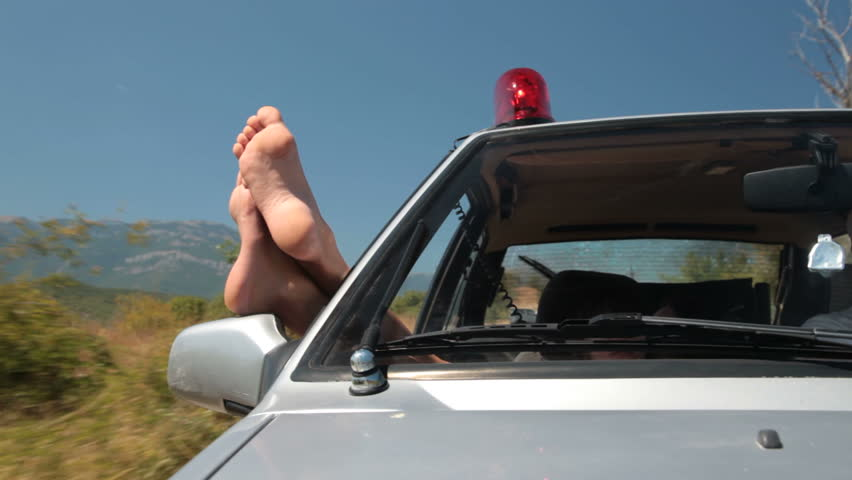 Woman hanging out legs from window riding  police car with siren - HD stock video clip