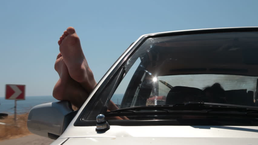 Female feet hanging out of the window riding car