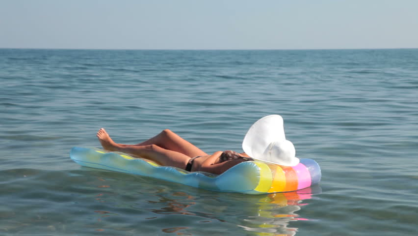 unrecognizable woman in bikini relaxing on raft - HD stock footage clip