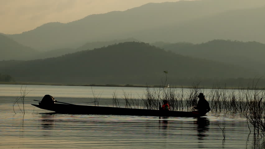 Fishermen rowing wooden canoe at sunset on bendiwewa lake for Paddle boat fishing