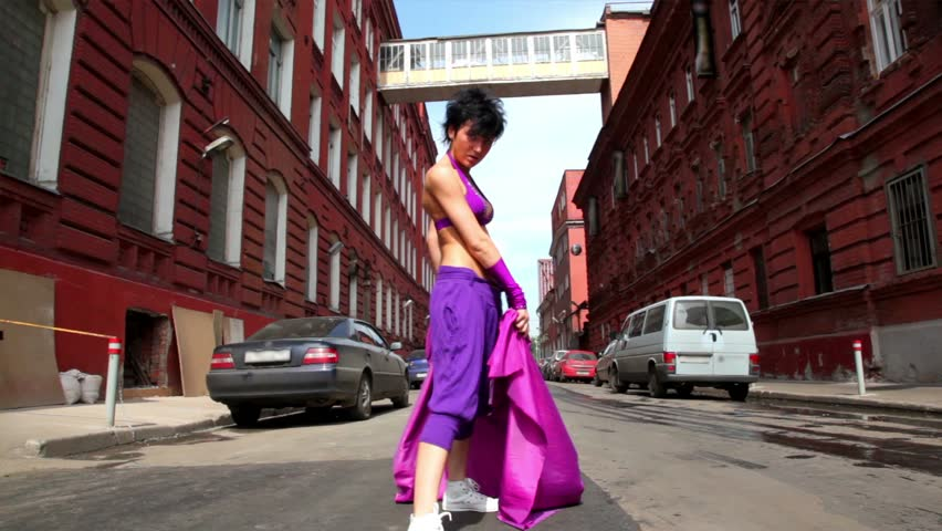 Girl dances in modern style with cloth on street between houses