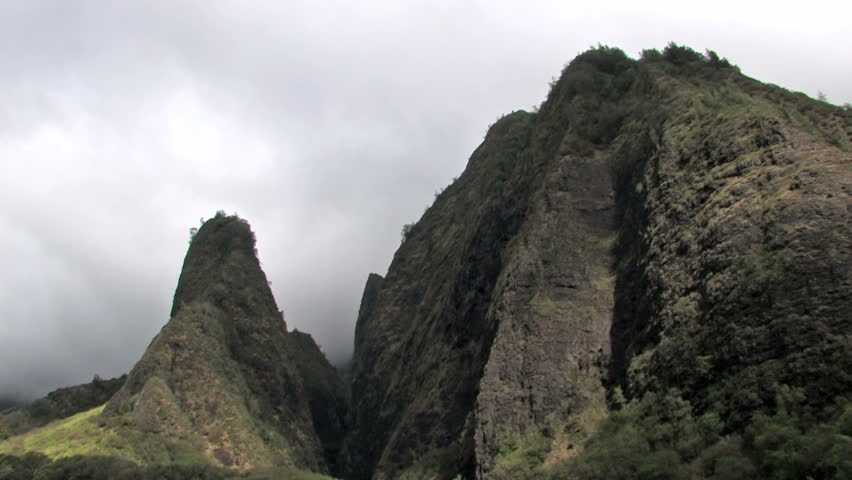 Iao Valley in Maui. Famous Needle covered in rain forest trees and vegetation. Mountains with clouds moving past peak. Tropical landscape in Hawaii. Fast moving clouds and shadows. - HD stock footage clip