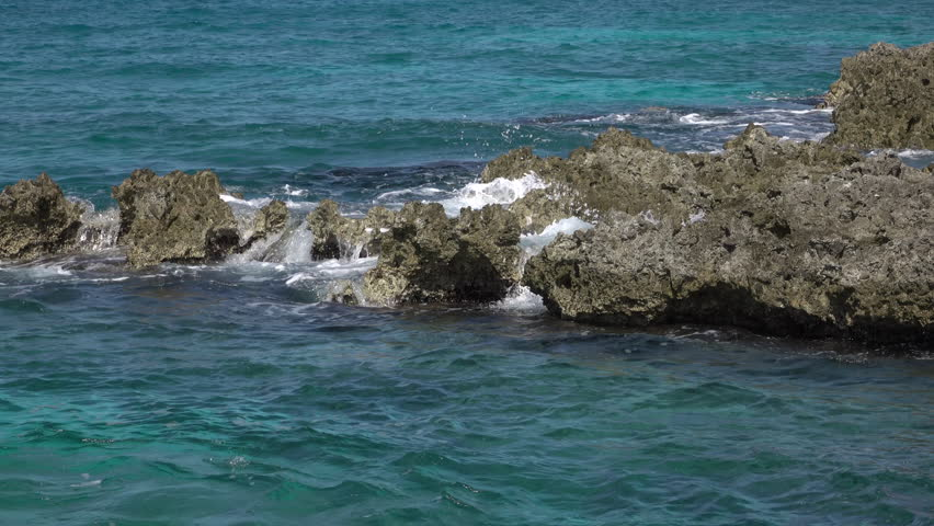 Grand Cayman Caribbean beautiful rocky shore waves. South western Caribbean is a destination for cruise ship and vacation travel. Beach, scuba diving and resorts on the island cater to tourists.