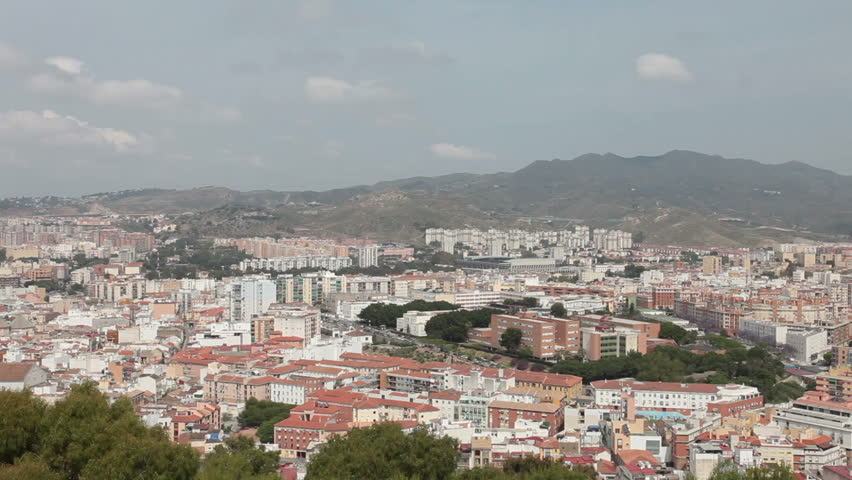 City of Malaga Spain pan from hill part of city to Mediterranean Sea port and harbor. Tall buildings and narrow roads on coast of Mediterranean Sea. Historic city from Gibralfaro Castle fortification. - HD stock footage clip