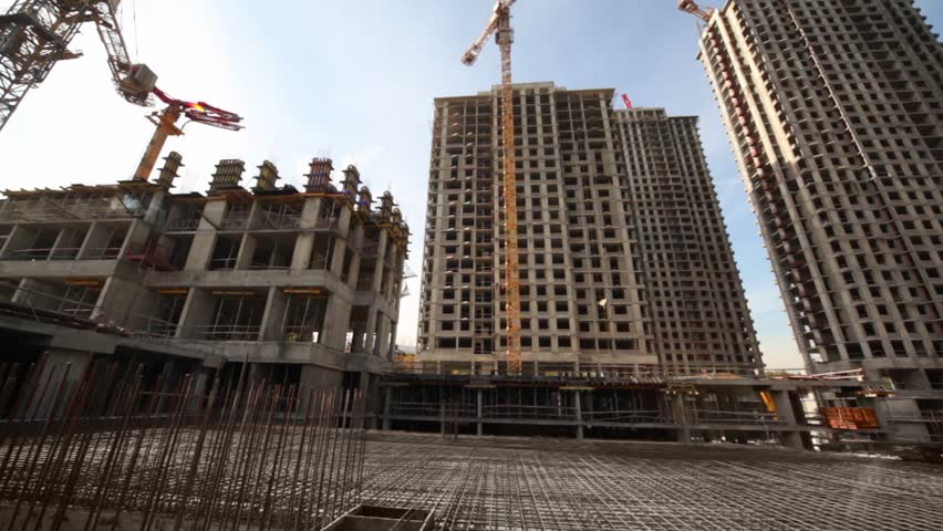 Metallic carcass in between unfinished tall buildings and cranes, panorama under blue sky