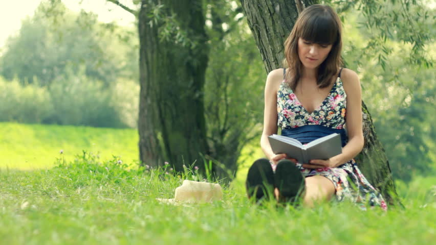 Young attractive woman reading book by the tree in park, dolly shot - HD stock footage clip