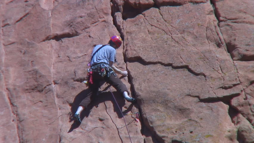 Placing blade piton with hammer in limestone crack while - Garden of the gods rock climbing ...