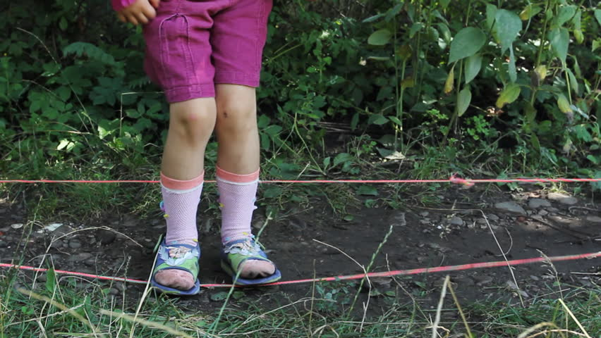 feet little girl jumps through two stretched rubber bands, then go away - HD stock video clip