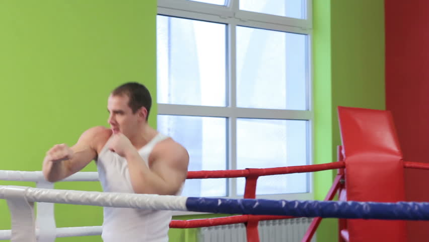 Boxing classes. Two men are working out blows in the ring