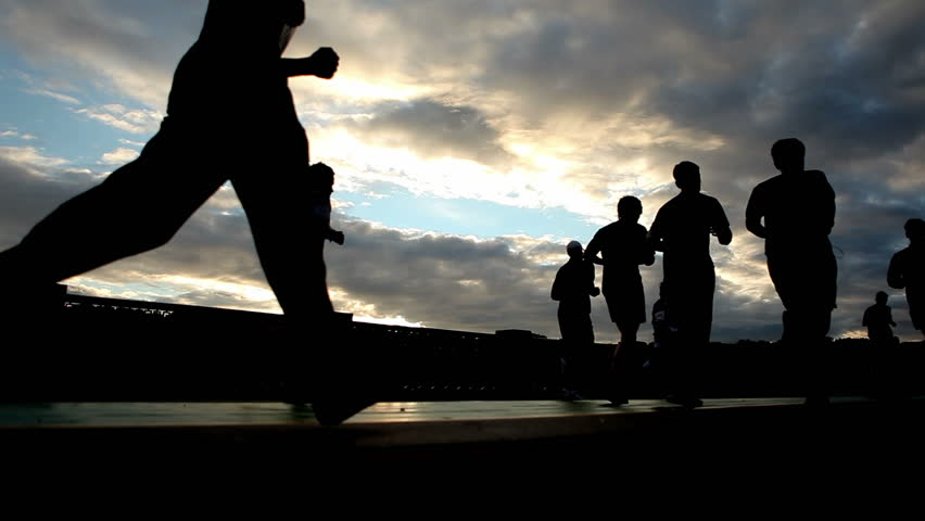 silhouettes of  running people on the background of the sunset sky