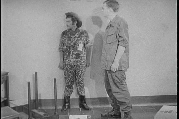 CIRCA 1960s - A United States Army interrogator picks an overturned table up and sets it right and invites a prisoner of war to sit own for his interrogation in 1968.