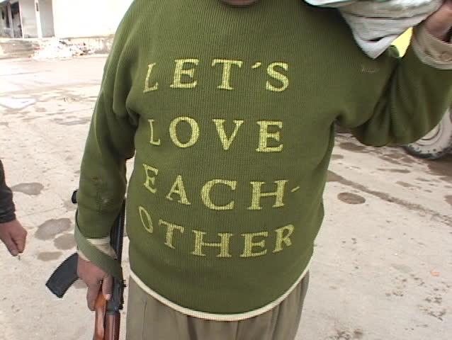 IRAQ - CIRCA 2003: An Iraqi man holding a rifle shows his shirt which says Lets Love Each Other circa 2003 in Iraq.