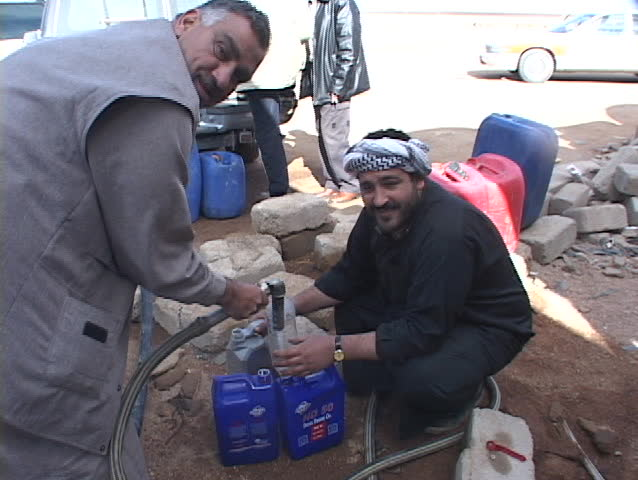 IRAQ - CIRCA 2003: Iraqi citizens siphon gas during the war's fuel shortage.