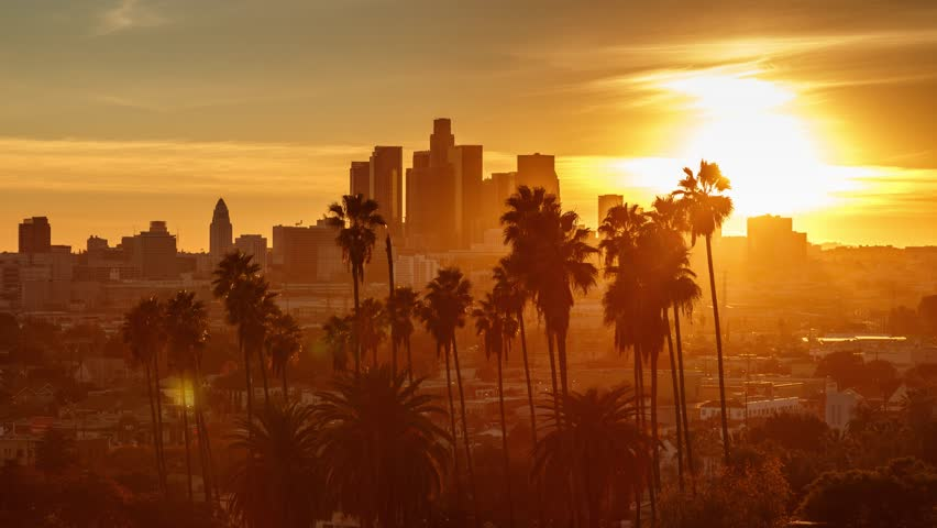 Beautiful sunset to night transition over city of Los Angeles downtown skyline with palm trees in foreground. 4K UHD timelapse.