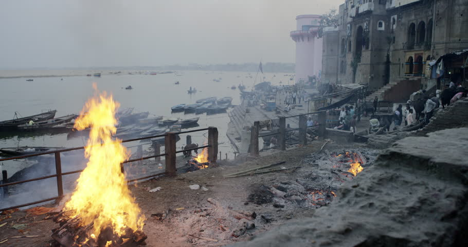 Varanasi, India - Cremation fire on Dasawamedha Ghat. Evening late afternoon Ganges river ghat people fire mystery smoke body temple ceremonies. Varanasi, India February 2016