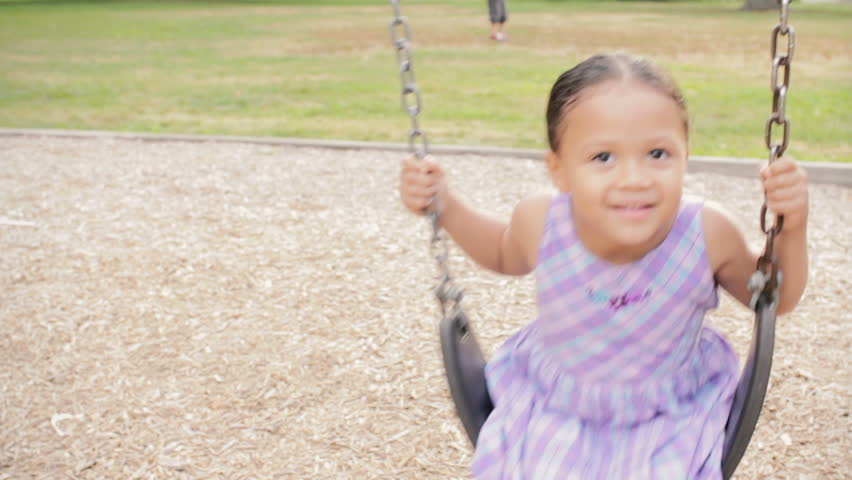 Healthy little preschooler girl playing on swing smiling