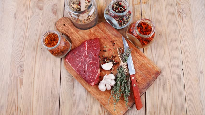 raw beef meat fillet with peppercorn and thyme and differnt spices in glass bottles ready to grill on wood figured aged board over table 1920x1080 intro motion slow hidef hd