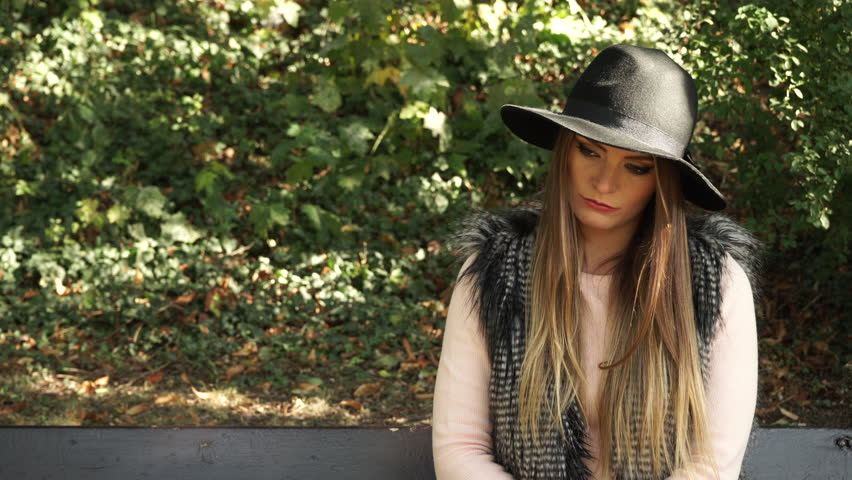 Woman outdoor. Fashionable autumn girl long hair wearing black hat sitting on bench in park waiting for someone and looking around, 4K with motorized slider. Prores HQ codec - 4K stock video clip