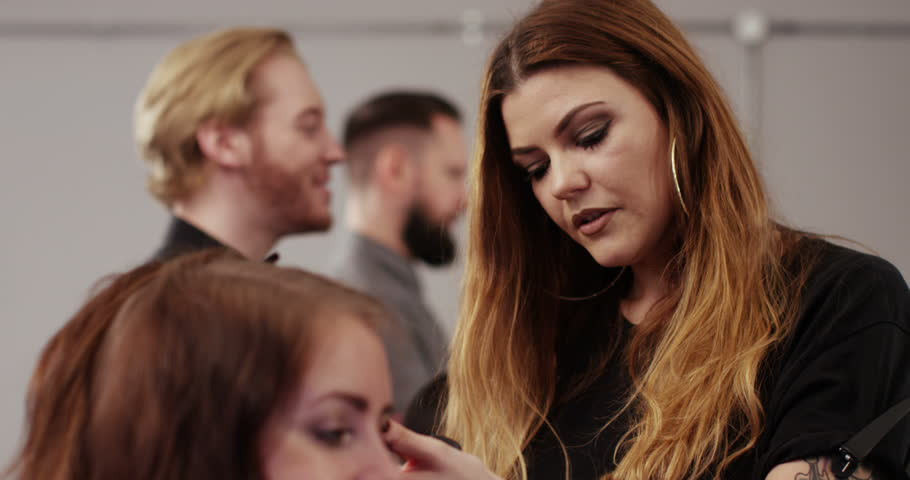 An attractive woman getting her hair styled in a salon. Shot on RED Epic in slow motion. - 4K stock video clip