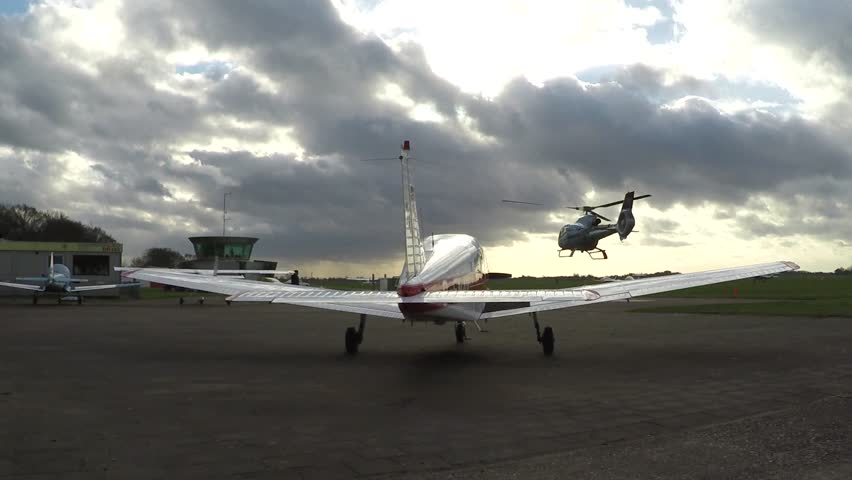 Airfield heavy large turbine helicopter taking off and flying away small recreational plane parked on tarmac in front of footage and an overcast sky in background heavy winds clouds moving fast 4k