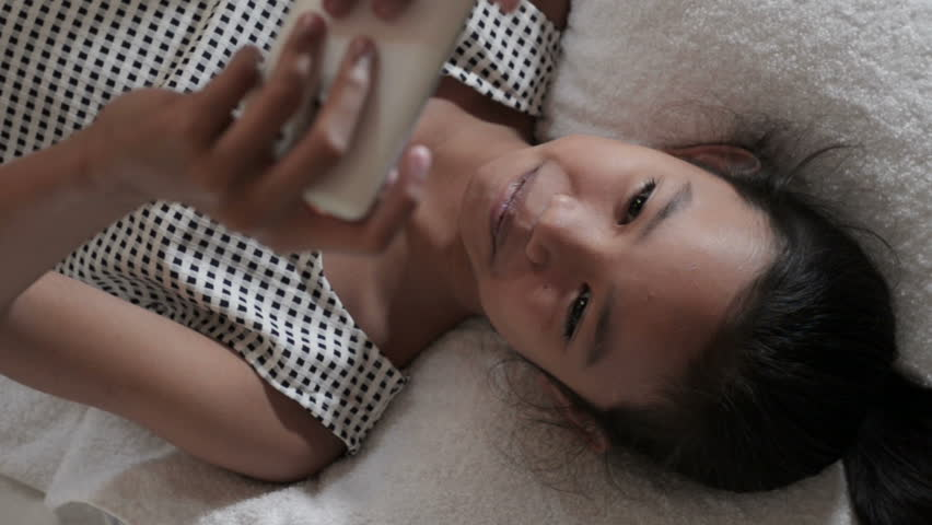 Happy girl lying on a bed laughing and smiling while reading on a cell phone. - HD stock video clip
