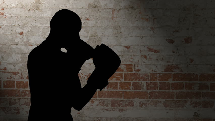 HD silhouette footage of a bald man wearing boxing gloves throwing various punches against a brick background
