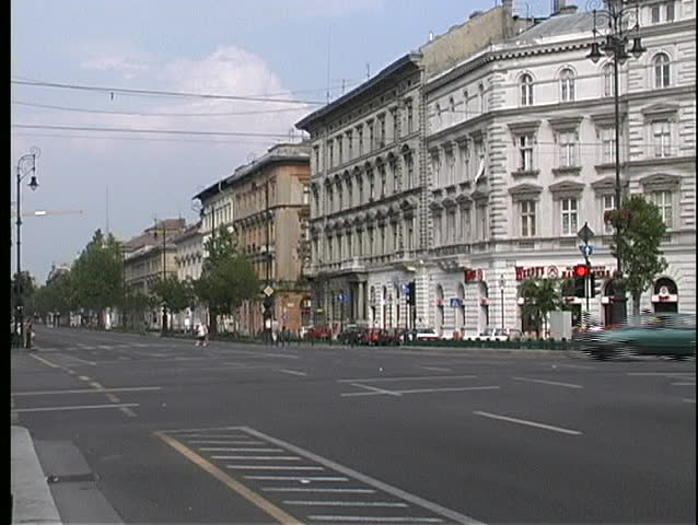 Traffic, trolleys, and trams drive past old buildings in Budapest.