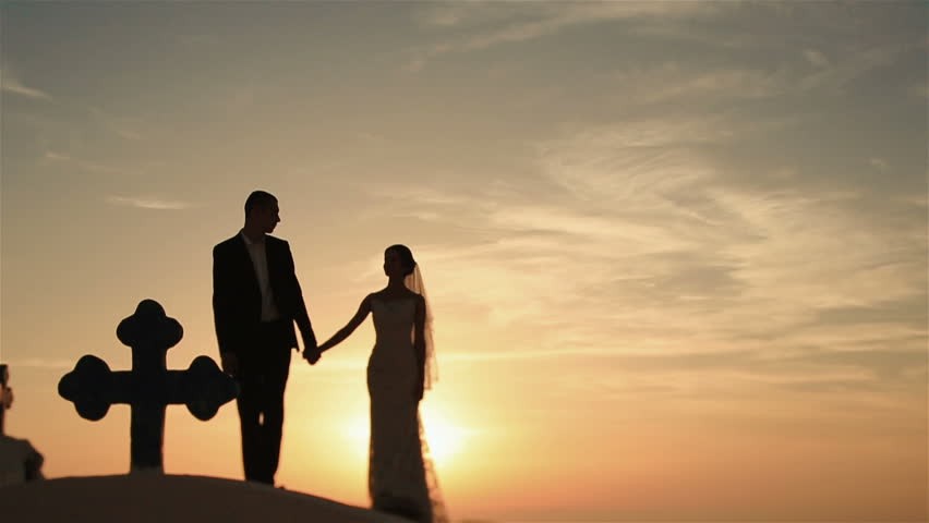 Happy married couple walkiing holding hands on church roof at sunset sky background | Shutterstock HD Video #14429326