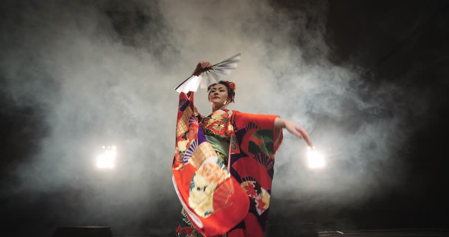 4K beautiful Japanese geisha dancing on stage and posing for the camera,the smoke in the background, slow motion | Shutterstock HD Video #14442808