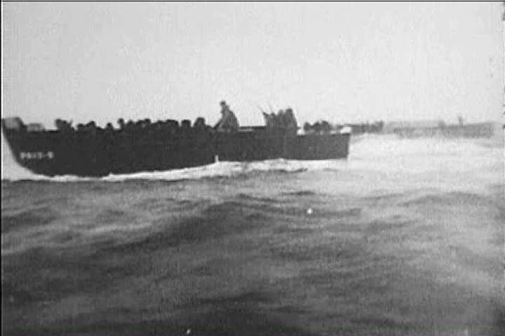 CIRCA 1940s - Boats carrying troops, including a vessel that sinks, rush toward the beaches of Normandy, landing, while bullets and bombs fly and explode all around them in 1944. - SD stock footage clip