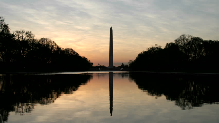 The Washington Monument is silhouetted against a colorful sky in Washington, DC - HD stock footage clip