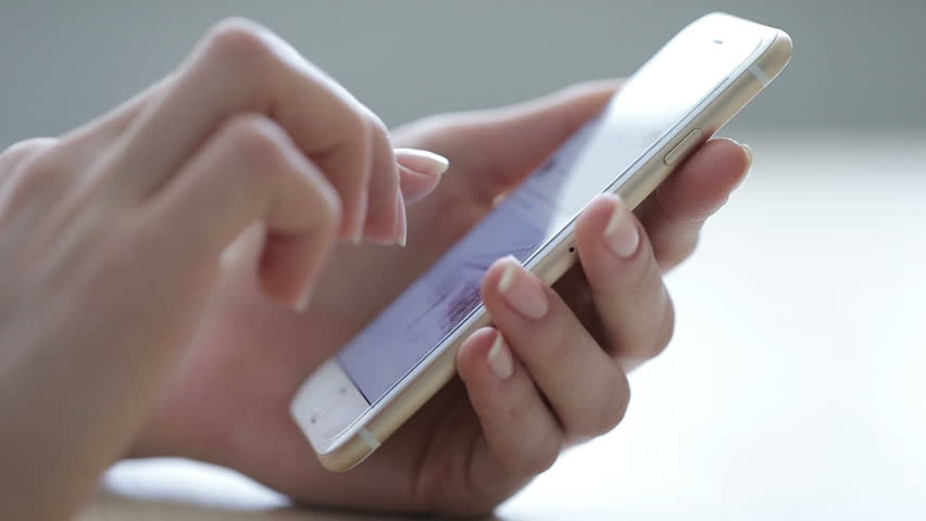 Closeup of young woman hands scrolling pictures phone. surfing internet | Shutterstock HD Video #14590471