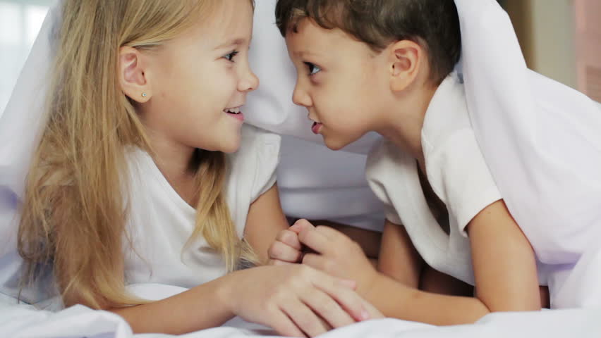 Lovely brother and sister lying in bed at home. Concept of Brother And Sister Together Forever       - HD stock footage clip