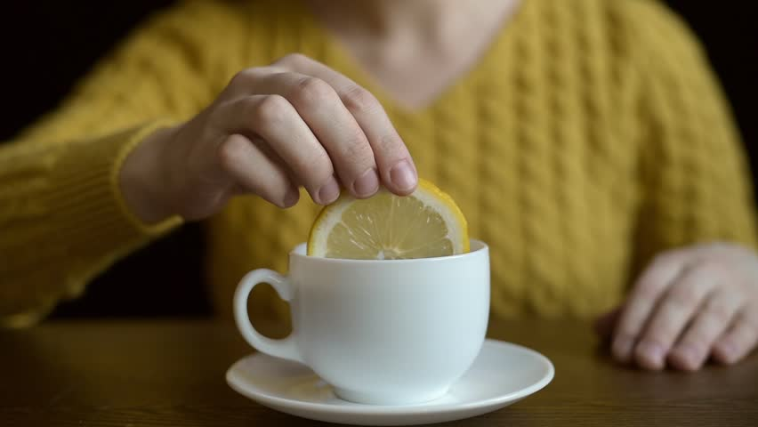 Woman putting lemon into a tea cup. No face can be seen.
