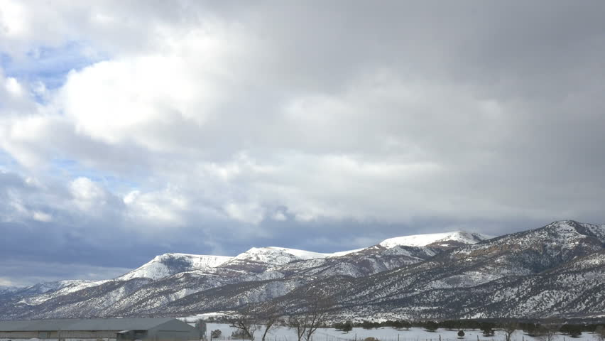 FOUNTAIN GREEN, UTAH - FEB 18, 2016:Time lapse- Grey cloud with sun lit highlights blowing rapidly over snowy mountains, farms and fields portending a coming storm. - HD stock footage clip
