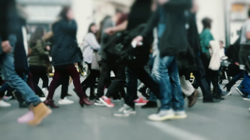 People pedestrians walk/cross big city intersection slow motion 100p.Gimbal stabilized tracking shot of an anonymous crowd mostly of young age getting across a busy city street.No logos/faces visible. - HD stock footage clip