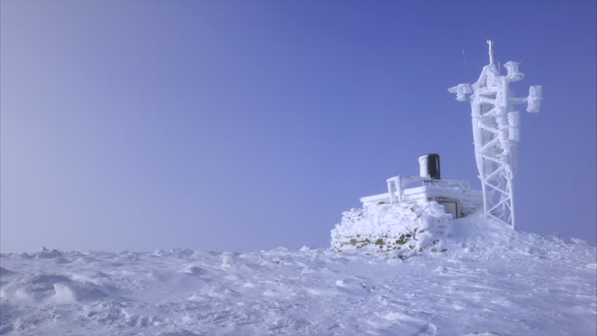 A hiker approaching a frozen weather station on the summit of Cairn Gorm in the Scottish Highlands on a cold sunny winters day. | Shutterstock HD Video #14679706
