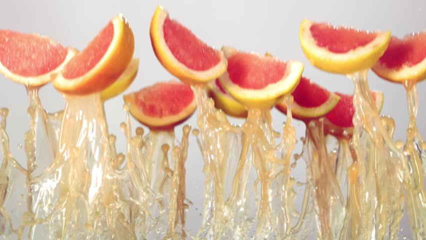 grapefruit slices fly with grapefruit juice, white background, slow motion #14720557