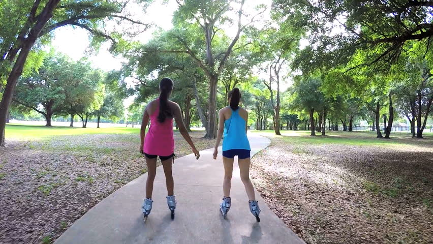Young active multi ethnic American girls roller skating outdoor