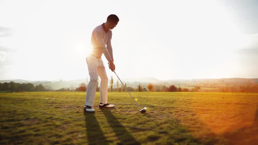 Golf Player plays golf on a beautiful summer morning. Backlite shot - HD stock footage clip