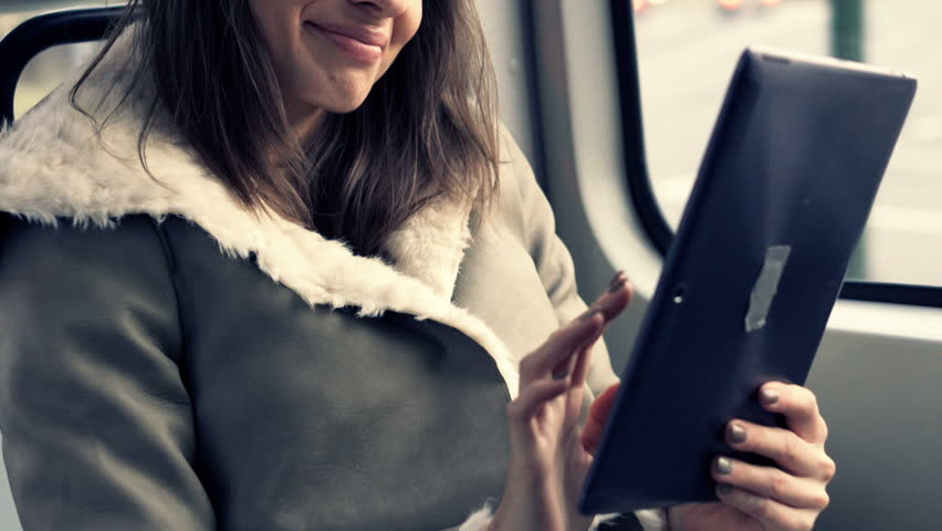 Young woman with tablet computer sitting on the tram