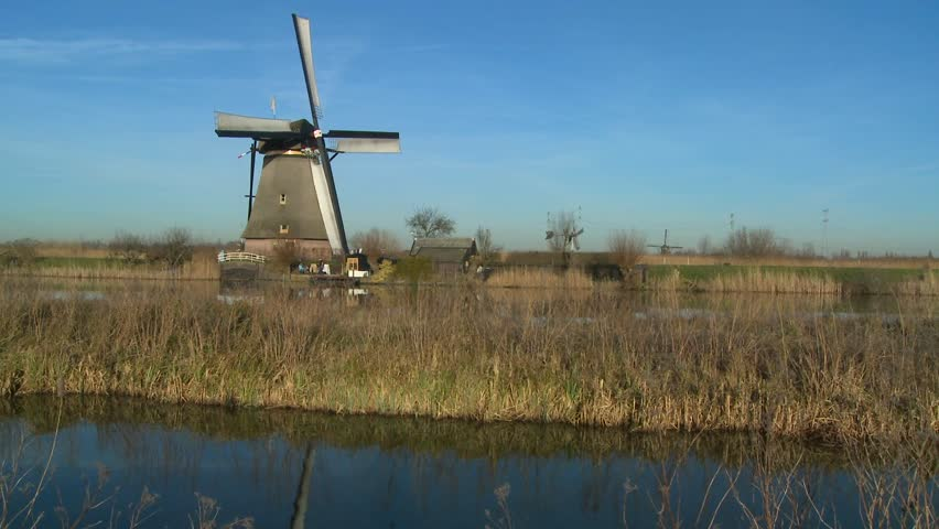 A windmill rises above a canal and grass in Holland. - HD stock footage clip