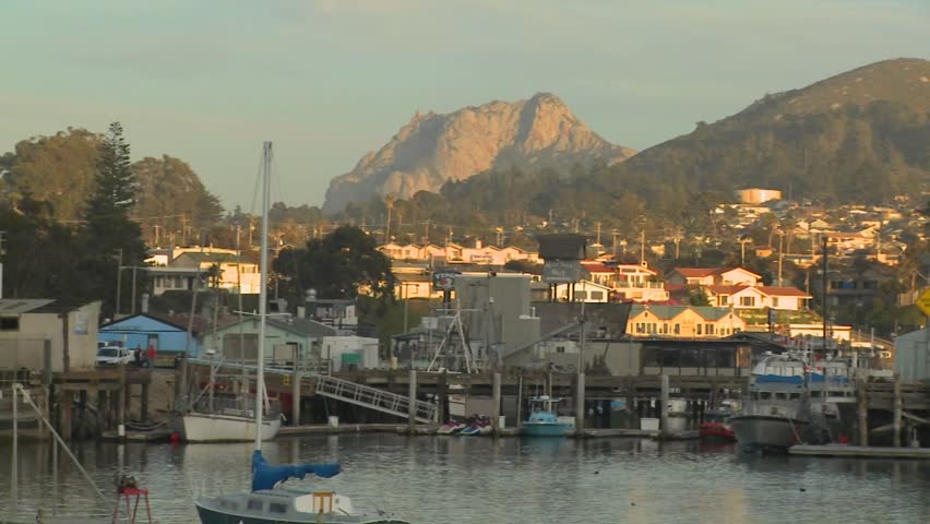 A pan across the small Central California town of Morro Bay with fishing boats in the harbor. - HD stock footage clip