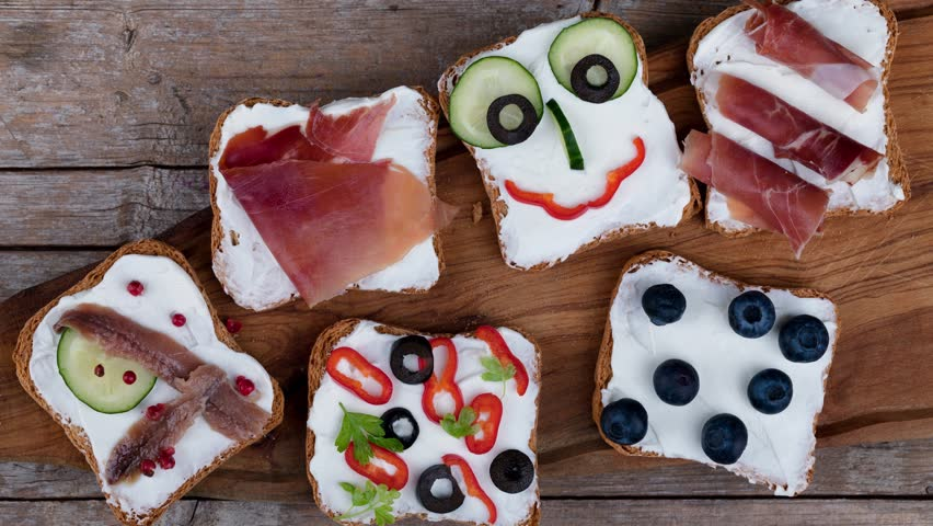 Video clip of various appetizers canape style on toasted bread with cheese, cucumbers, olives, red peppers and ham.