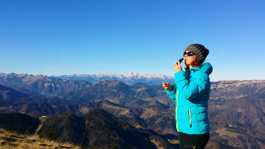 4K, Pretty middle aged woman hiker with hip flask, pauses at the top of a high mountain in Alps, Triglav mountain in background, sounds of wind, 3840x2160, 2160p, ULTRA HD